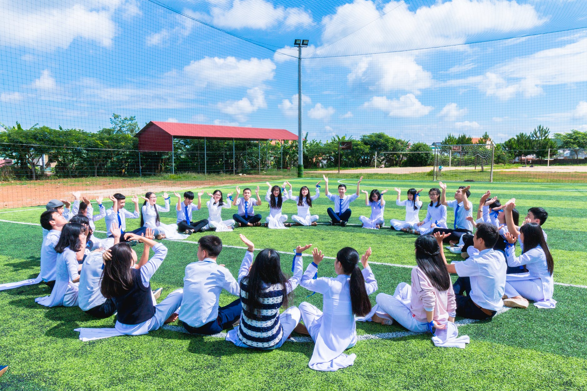 people sitting on green lawn grass while doing hands up at daytime