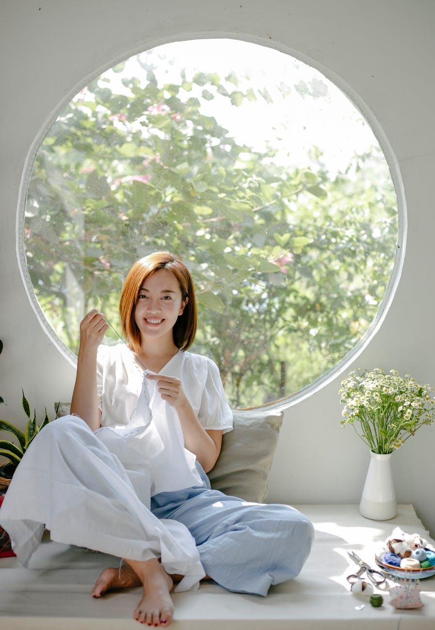 happy asian woman sewing near window