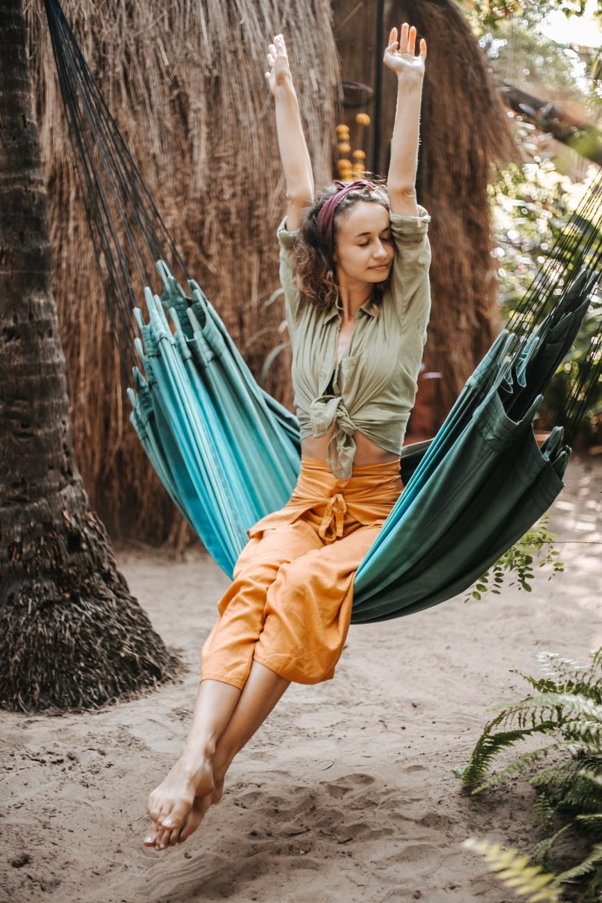 a woman sitting on a hammock and stretching
