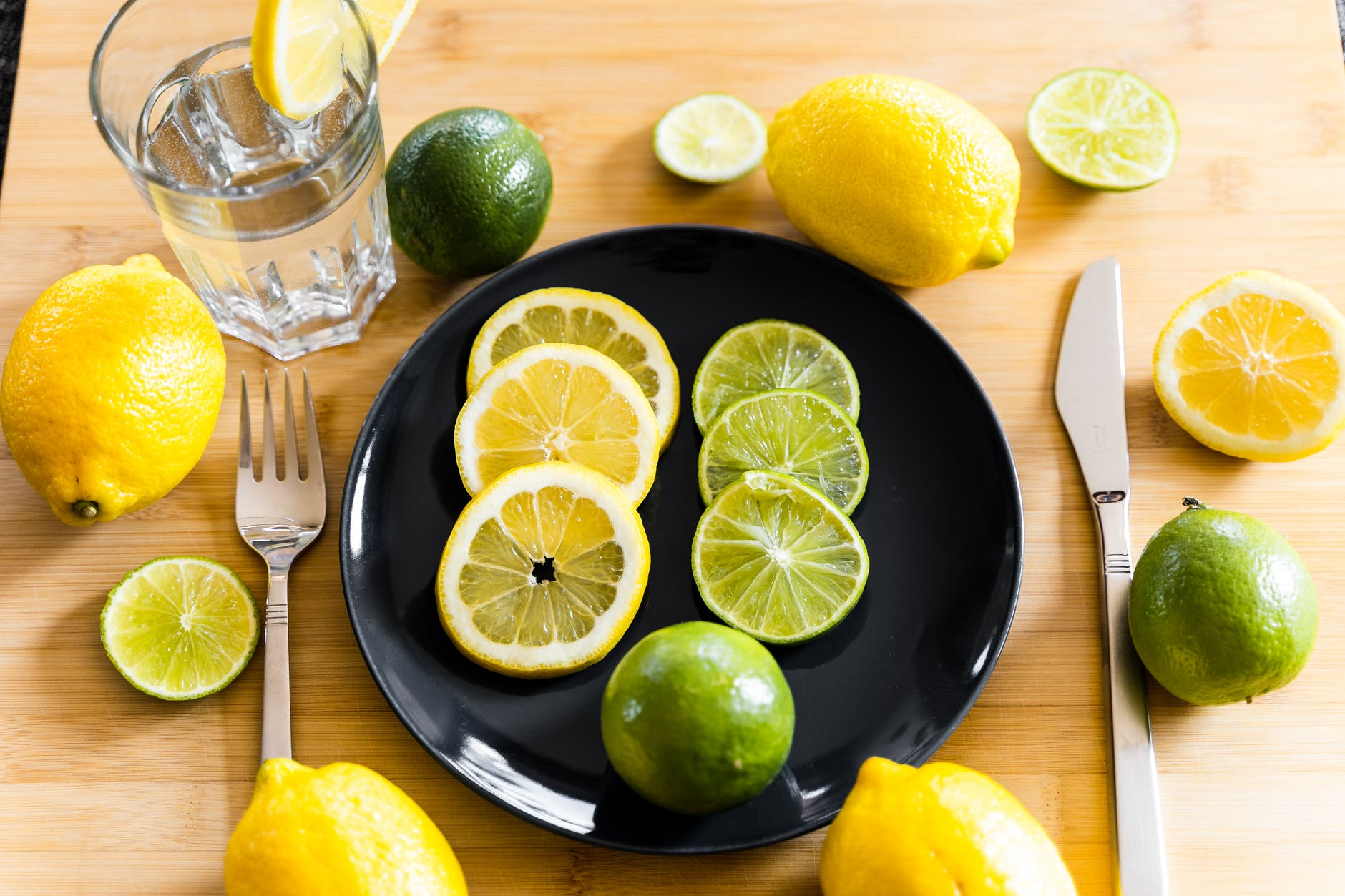 fresh lemons and limes arranged on table with plate and water glass