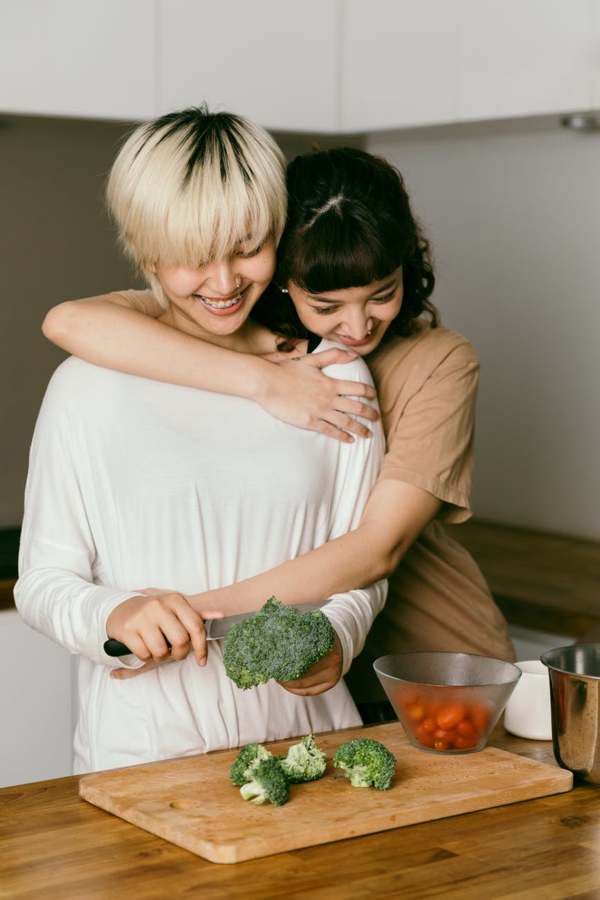 woman being hugged while making dinner