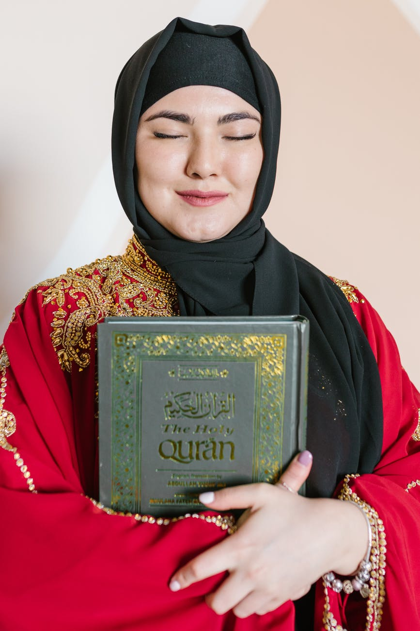 woman in black hijab holding a holy book