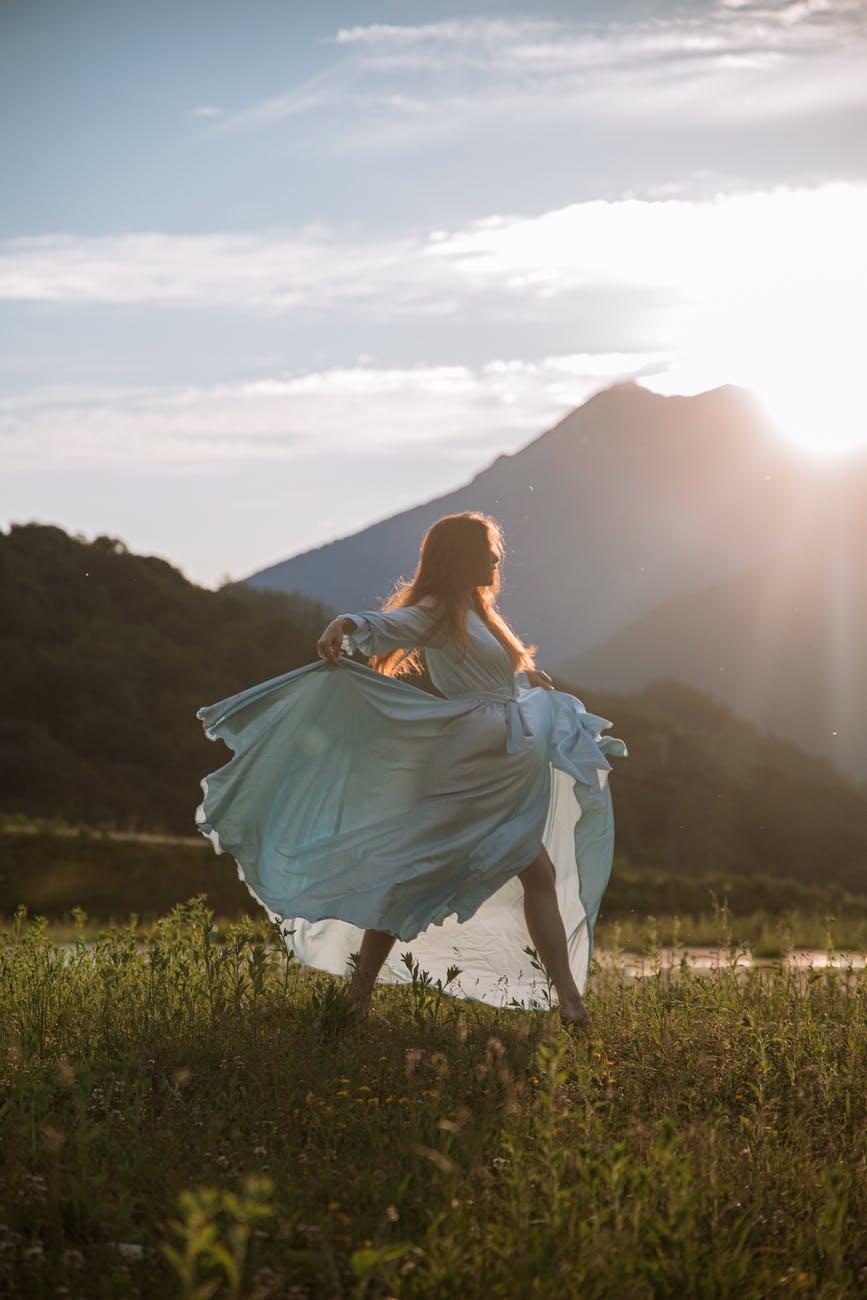 woman in blue dress standing on green grass field